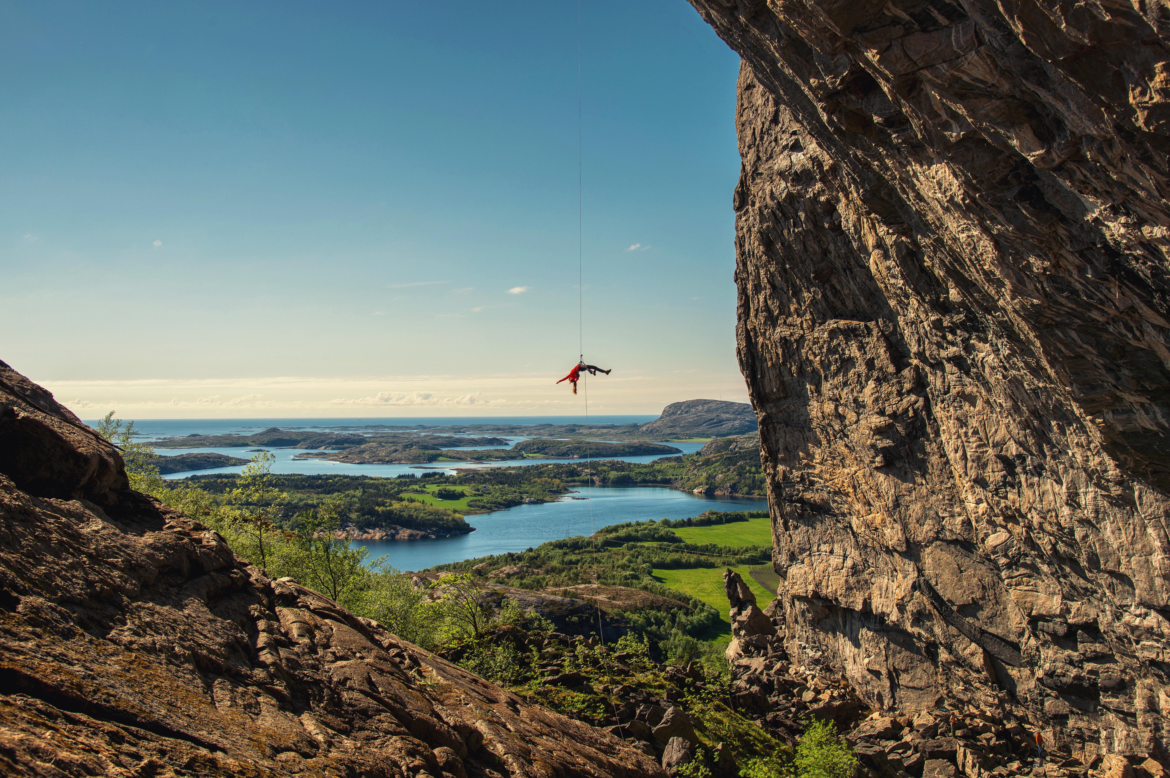 Hanshelleren - Unik klatrevegg i Flatanger. En person henger i tau ved Hanshelleren. Sommer.