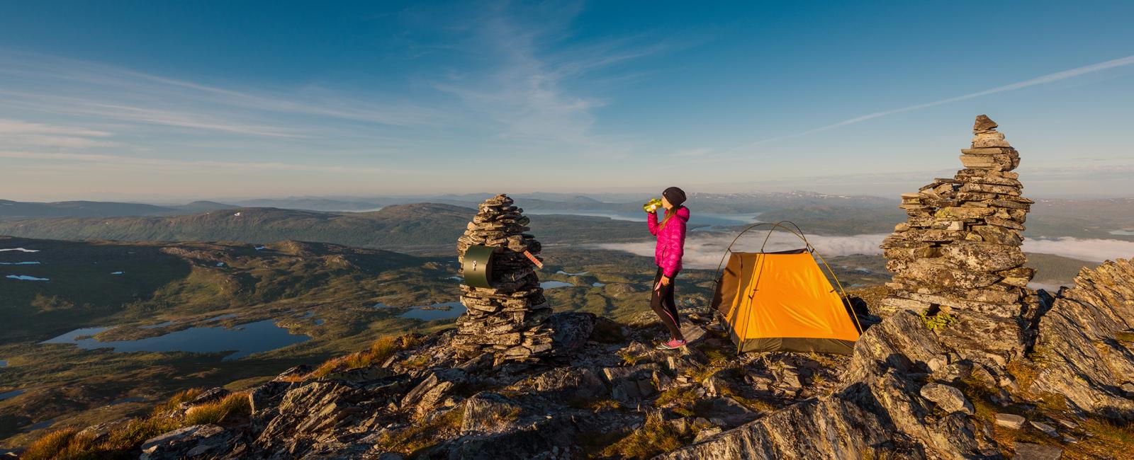 Jente med telt på toppen av Dærga, en av flere fjellturer i Røyrvik. Foto: Bernartwood