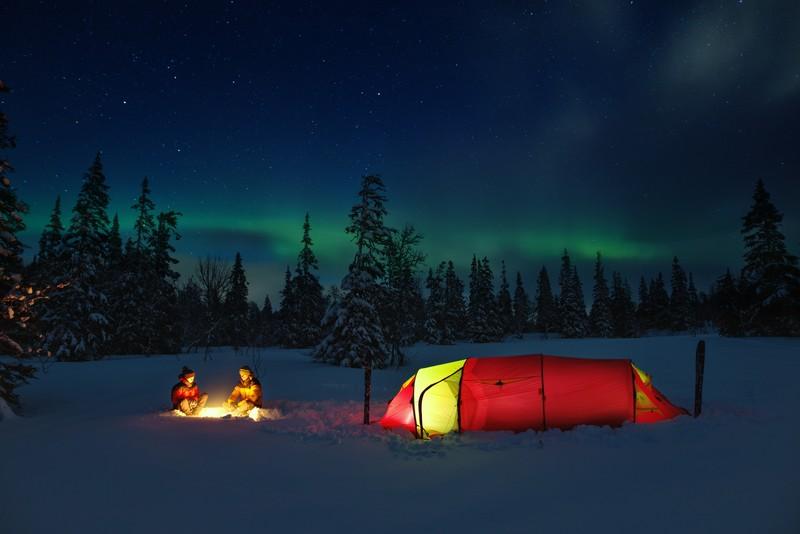 To mennesker rundt bål og telt i Lierne nasjonalpark, Namdalen, Trøndelag.