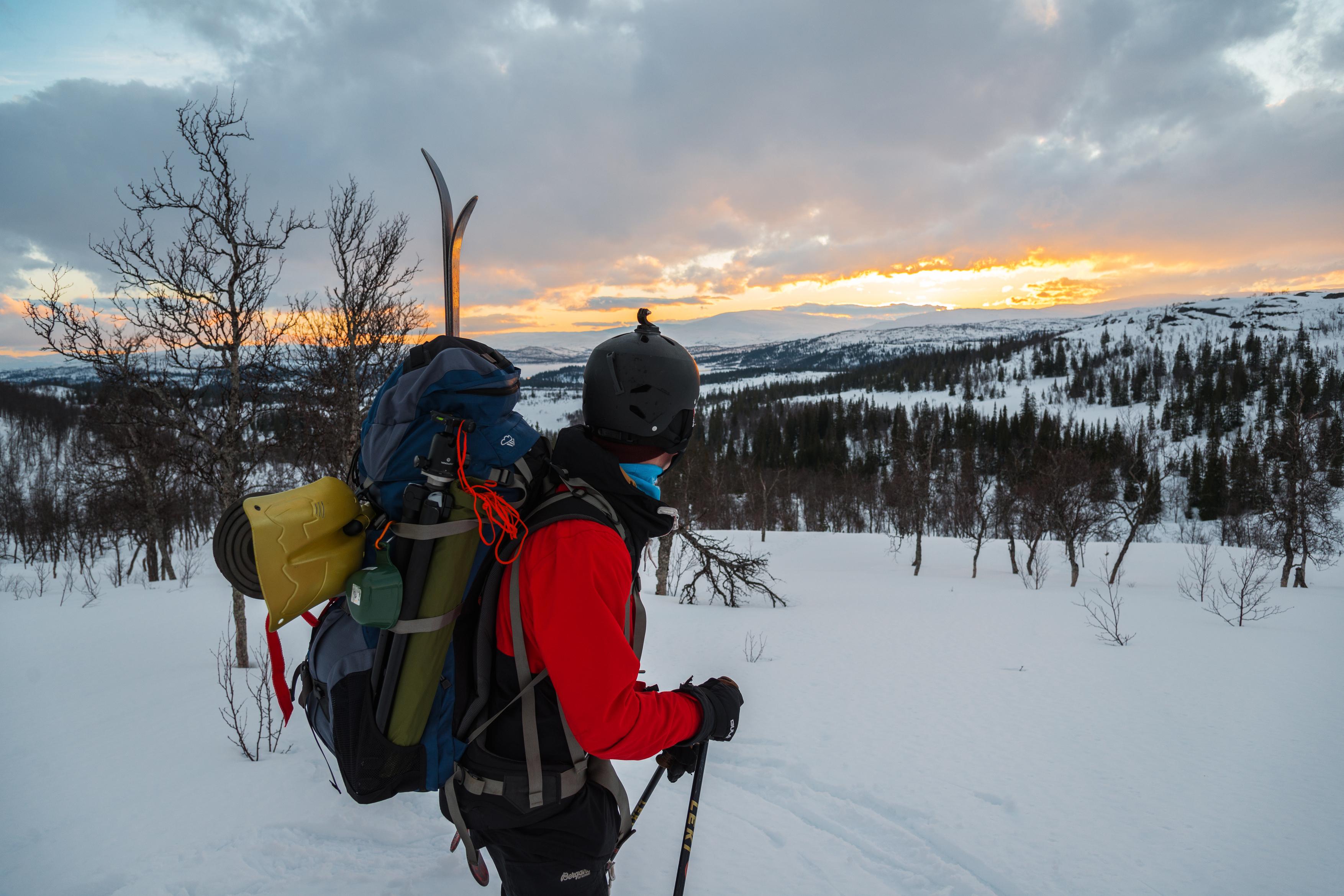 Mann med sekk og rød anorakk ser utover snødekt landskap i Røyrvik.